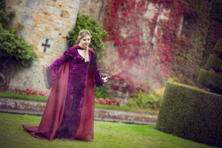 a beautiful young women with Down syndrome stands in a stunning long purple gown with a golden headpiece, in front of the purple wall of Hever castle.